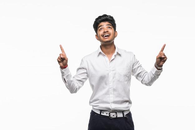 Aziatische indische mens met vingerpunt dat naar omhoog op witte muur wordt geïsoleerd