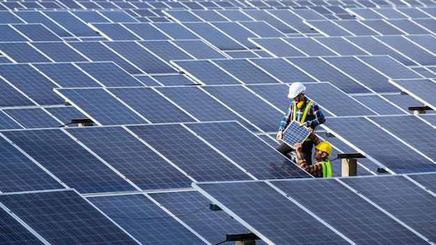 Aziatische ingenieur bezig met het controleren van apparatuur in zonne-energiecentrale, pure energie, hernieuwbare energie