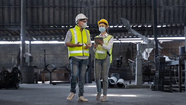 Aziatische ingenieur controleert productieproces op fabrieksstation door veiligheidsmasker te dragen ter bescherming tegen vervuiling en virussen in de fabriek tijdens covid-19 pandemi