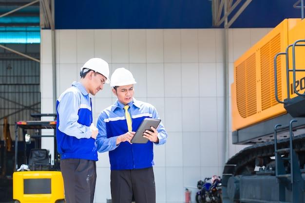 Aziatische ingenieur die bouwmachines van bouwplaats controleert