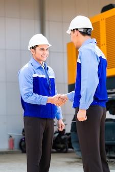 Aziatische ingenieur die overeenkomsthanddruk heeft bij bouwmachines van bouwplaats of mijnbedrijf