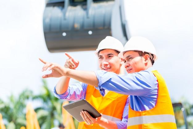 Aziatische ingenieur die plannen bespreken op bouwwerf