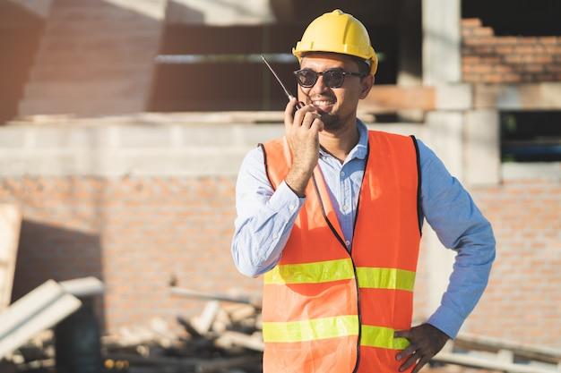Aziatische ingenieur die radio gebruiken om team in bouwconstructie te belasten.