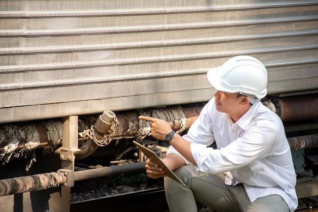 Aziatische ingenieur die veiligheidshelm met het controleren van trein voor onderhoud draagt