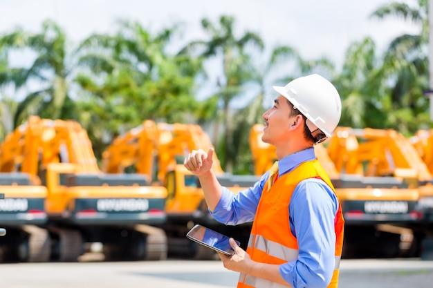 Aziatische ingenieur plannen op bouwplaats controleren