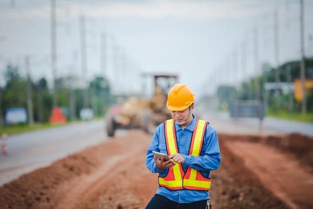 Aziatische ingenieurs kijken toe op de wederopbouw van wegen en inspecteren de aanleg van de weg op de bouwplaats.