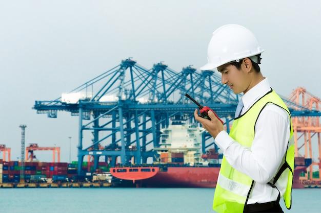 Aziatische ingenieurs voor de mannen van de scheepvaarthaven. met behulp van radio met werk de hele tijd.