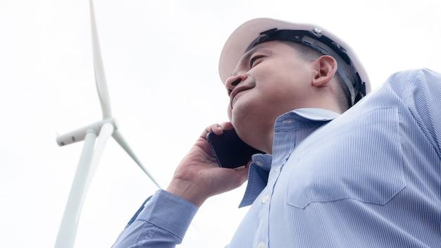 Aziatische ingenieurswindmolens die smartphone gebruiken met de windturbine op de achtergrond.16:9-stijl
