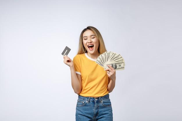 Aziatische inhoud vrouw met ventilator van geld dollar bankbiljetten en creditcard