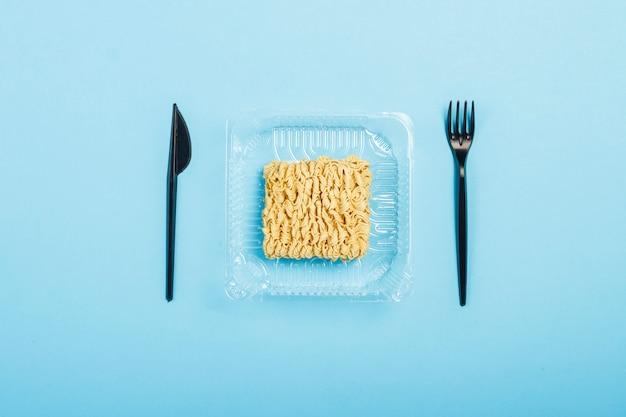 Aziatische instantnoedels en plastic wegwerpschalen op een blauwe ondergrond. het concept gemaksvoedsel, fast food, junk food. plat lag, bovenaanzicht.