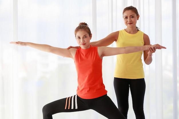 Aziatische instructeur die vrouwelijke nieuwkomersstudent ondersteunt die warrior pose doet tijdens yogasessie in studio