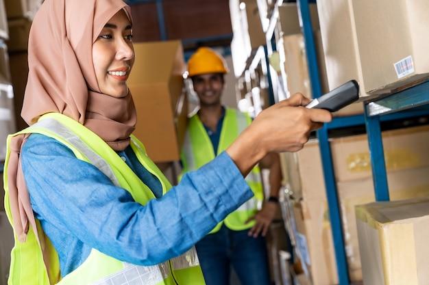 Aziatische islam moslim vrouwelijke magazijnmedewerker inventaris doen met barcodescanner