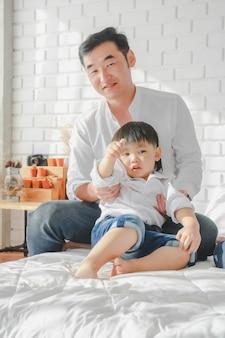 Aziatische japanse de moederzoon die van de familievader wit overhemds dragend kind op slaapkamer in witte ruimte dragen.