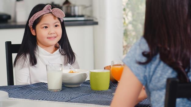 Aziatische japanse familie ontbijt thuis. aziatische moeder, vader en dochter voelen zich gelukkig samen praten terwijl brood, cornflakes granen en melk in kom op tafel in de keuken in de ochtend eten.