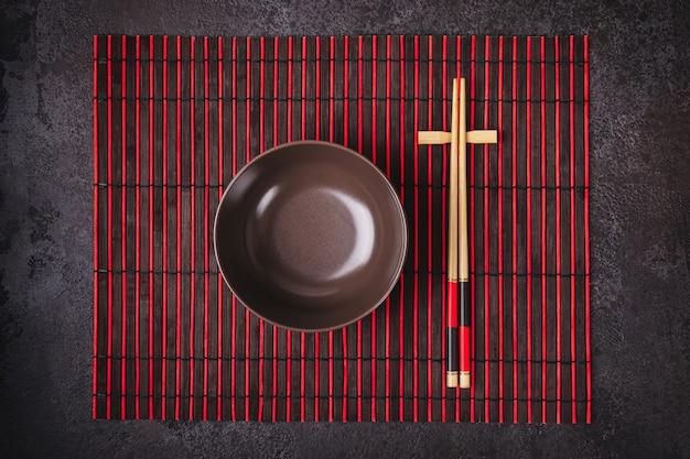 Aziatische japanse tafel setting. bamboestokjes en kom op gestreepte mat.