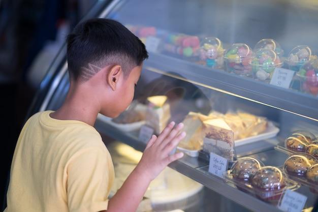 Aziatische jong geitjejongen die bij bakkerijwinkel wachten en bakkerij kiezen die hij houdt van