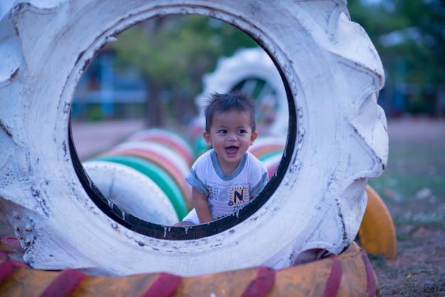 Aziatische jong geitjejongen die pret op het beklimmende stuk speelgoed van kinderen bij schoolspeelplaats hebben te spelen