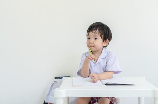 Aziatische jong geitjezitting om thuiswerk na school te doen