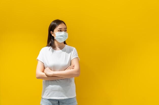 Aziatische jonge aantrekkelijke vrouw die een beschermend hygiënemasker over haar gezicht draagt om griep en virus te beschermen. onwel griep in besmet vrouwenportret met gele achtergrond. covid19 en coronavirus.