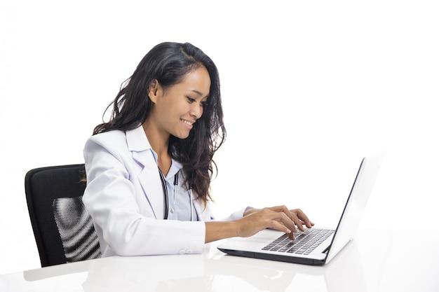 Aziatische jonge arts die en aan haar laptop glimlacht werkt