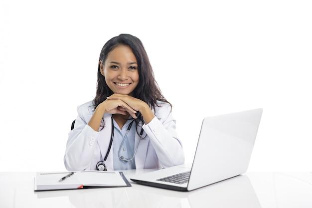 Aziatische jonge arts die terwijl het zitten op haar werkruimte glimlacht