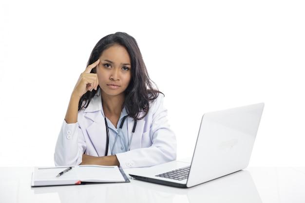 Aziatische jonge arts met vlakke uitdrukking terwijl het zitten op haar wo