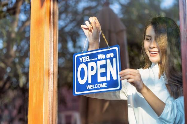 Aziatische jonge aziatische vrouw die een open bord bij de winkelglazen zet om de klant te verwelkomen