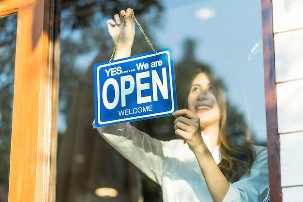 Aziatische jonge aziatische vrouw die open teken plaatsen bij de winkelglazen voor welkom de klant binnen in de koffiewinkel