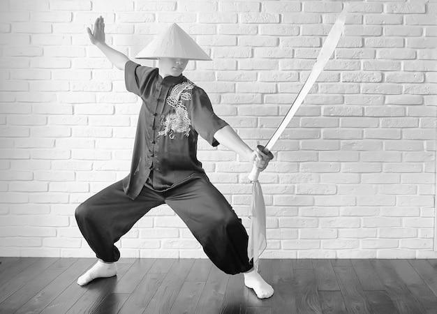 Aziatische jonge beginner op een witte bakstenen muurachtergrond