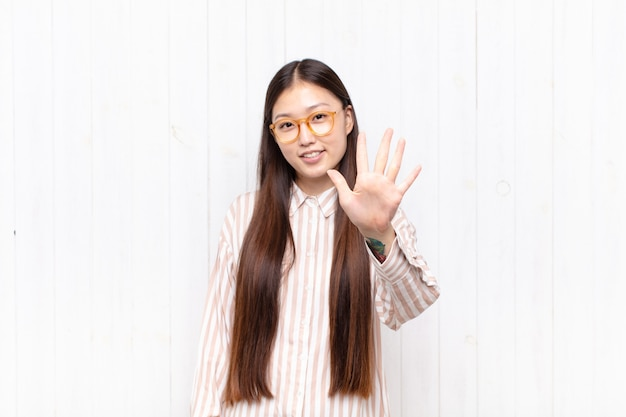 Aziatische jonge en vrouw die vriendelijk glimlacht kijkt, nummer vijf of vijfde met vooruit hand toont, aftellend