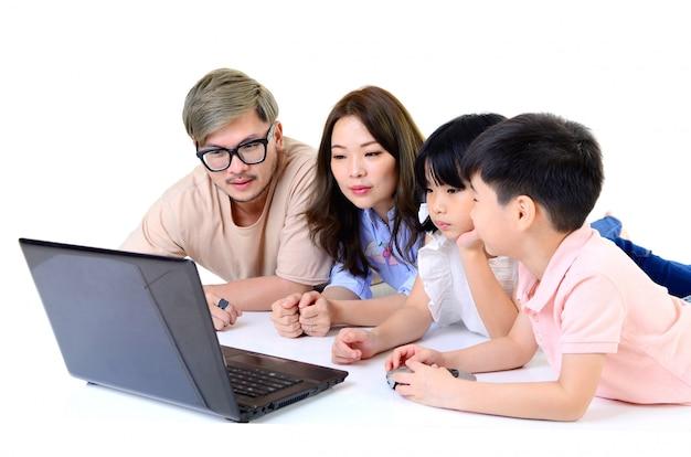 Aziatische jonge familie die laptop helemaal met behulp van