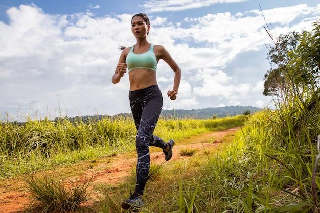 Aziatische jonge fitness vrouw oefening die bij bossleep loopt.