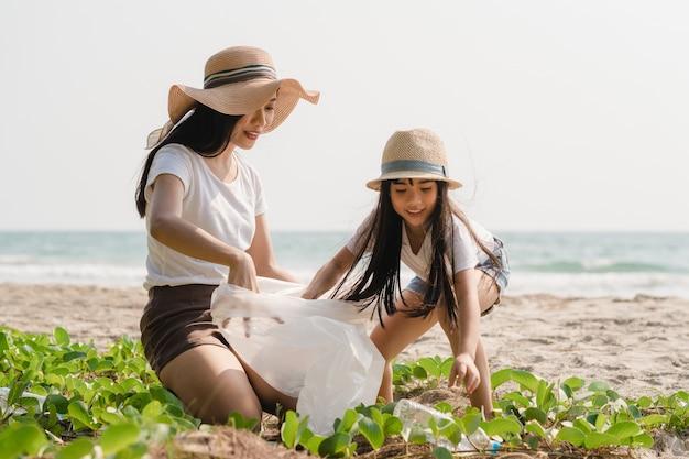 Aziatische jonge gelukkige familie-activisten die plastic afval op strand verzamelen. azië-vrijwilligers helpen de natuur schoon te houden en vuilnis op te halen. concept over milieuvervuiling problemen.