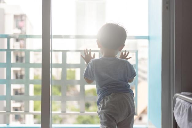 Aziatische jonge jongen die het venster opent