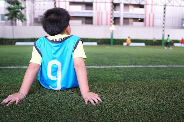 Aziatische jonge jongen die op de ondergeschikte voetbaltraining wacht.