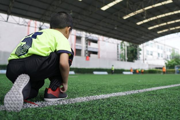 Aziatische jonge jongen die op het de sportgebied van voetbalgras voorbereidingen treft.
