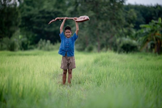 Aziatische jonge jongen met gitaar met de hand gemaakt in het openlucht, het levensland