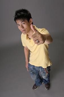 Aziatische jonge kerel geeft je een uitstekend teken