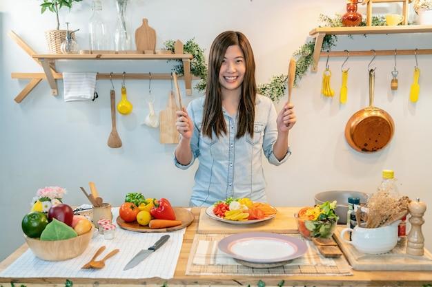 Aziatische jonge koken en presenteren de salade op de plaats in de moderne keuken