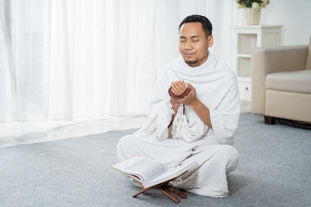 Aziatische jonge man bidden met al-qur'an en gebedssnoer