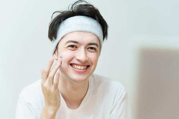 Aziatische jonge man die crème op zijn gezicht aanbrengt