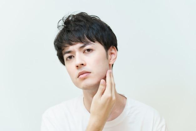 Aziatische jonge man die huidconditie controleert