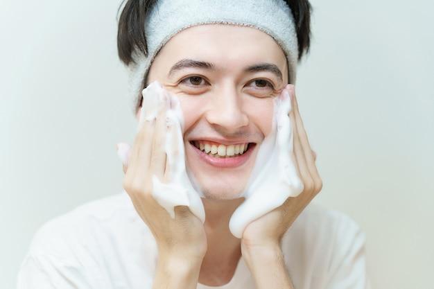 Aziatische jonge man die zijn gezicht wast
