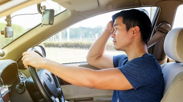 Aziatische jonge man een auto rijden en slaperig voelen.