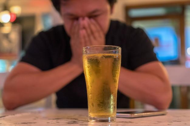 Aziatische jonge man in eenzame en depressieve actie en gezicht in handen te houden en glas te zien