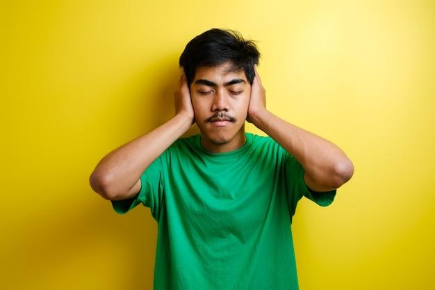 Aziatische jonge man in groen t-shirt sluit zijn oren met beide handen tegen gele achtergrond