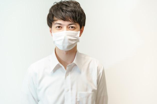 Aziatische jonge man in wit overhemd en masker