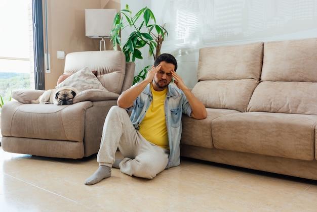 Aziatische jonge man met een depressie zittend op de vloer thuis