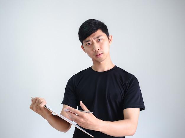 Aziatische jonge man met een houten klembord en een zilveren pen in de hand, een serieus gezicht kijkt naar de camera op wit