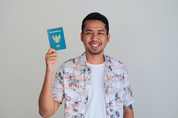 Aziatische jonge man met een strandoverhemd glimlachend gelukkig terwijl hij het paspoortdocument van het indonesische land laat zien